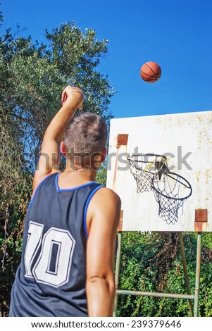 lefty basketball player shooting in an outdoor playground - stock photo
