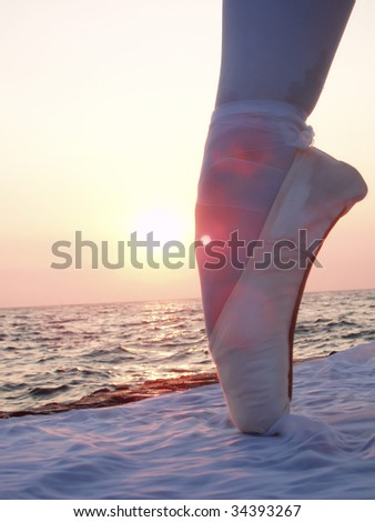 Leg in pink satin ballet shoes - stock photo