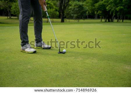 leg of golfer putting golf ball on green with copy space