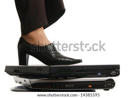 Leg of woman in elegant shoe stands on computers - isolated on white background - stock photo