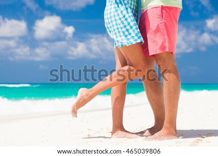 leg view of romantic couple hugging at the tropical beach