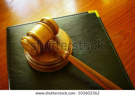 Legal gavel and leather binder on a desk - stock photo