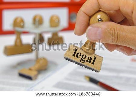 legal marked on rubber stamp in hand - stock photo