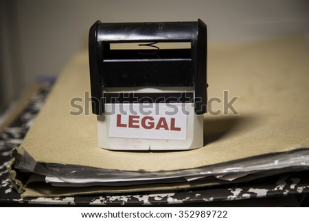 Legal word on a stamp on a big folder of paperwork - stock photo