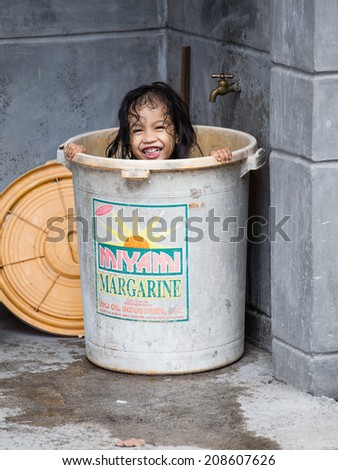 LEGAZPI, PHILIPPINES - MARCH 18, 2014: Unidentified homeless girl bathes in a plastic bucket of margarine. Nearly one of every three Filipino children aged 4 to 10 is underweight - stock photo