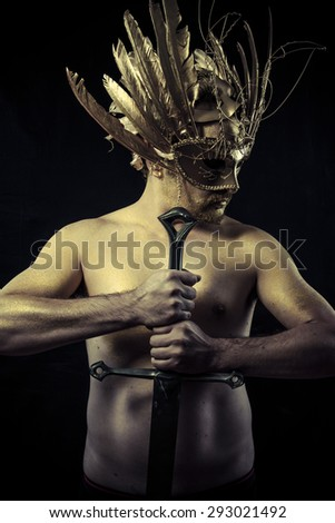 Legend, Warrior with helmet and sword with his body painted gold dust - stock photo