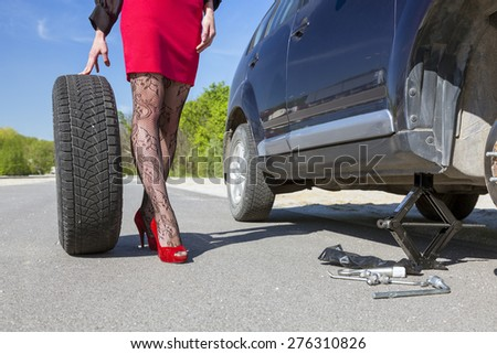 Leggy female changing wheel of car. Lady dressed in provocative clubbing pantyhose and bright red shoes high heels mini skirt rolls large wheel to car fixed on jack-screw with some tools - stock photo