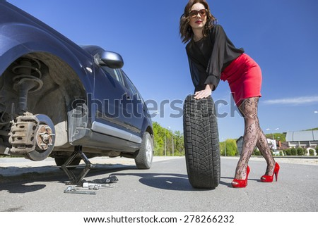 Leggy female changing wheel of car. Lady dressed in provocative clubbing pantyhose and bright red shoes high heels mini skirt rolls large wheel to car fixed on jack-screw with some tools