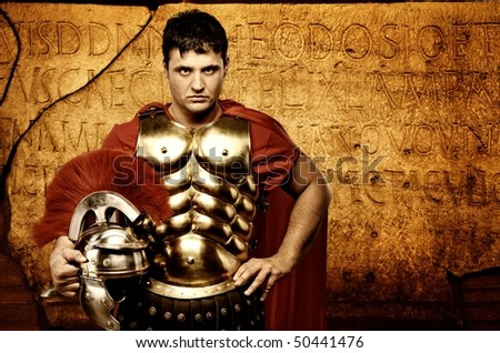 Legionary soldier in front of roman wall - stock photo