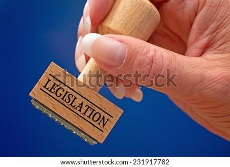 Legislation - female hand with stamp - stock photo