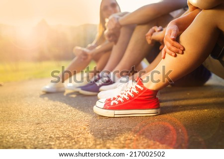 Legs and sneakers of teenage boys and girls sitting on the sidewalk - stock photo