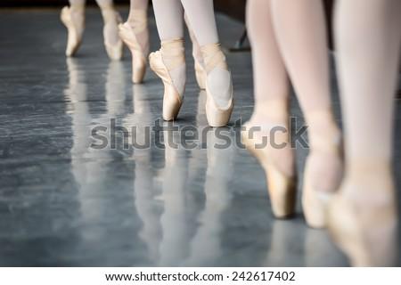 Legs dancers on pointe, near the choreographic training machine. - stock photo