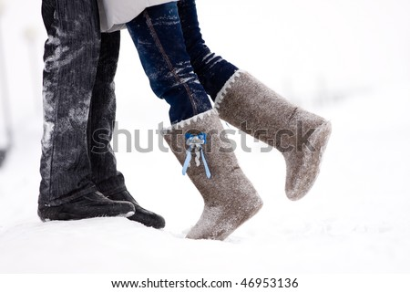 legs embracing couples standing on the snow snowy winter in the middle of the field - stock photo