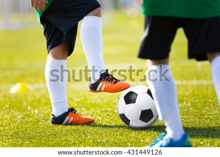 Legs feet of football player in white sports socks orange shoe and green shirt kicking soccer ball. Training session on green fresh grass for youth football soccer team.