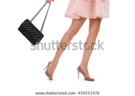 Legs in beige heel shoes. Lady's bag with chain strap. Expensive leather accessory. Glossy heels and pink dress.