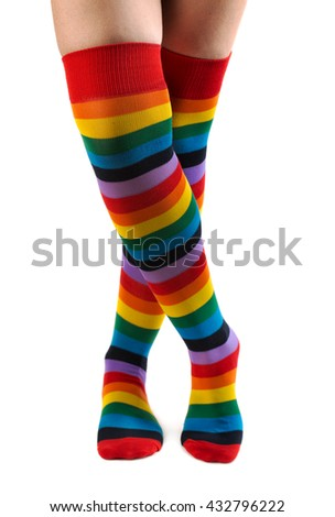 Legs in colored striped socks. Isolate on white background - stock photo