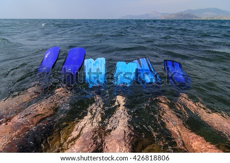 legs in flippers immersed into the sea - stock photo