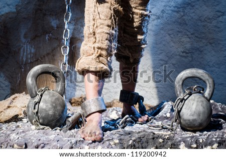 Legs in heavy iron shackles - stock photo