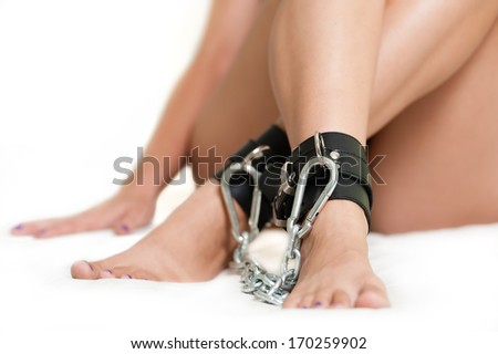 Legs in shackles on white - stock photo