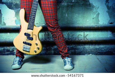 Legs in trousers and a guitar on a background of an old wall. - stock photo