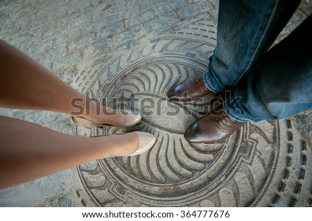 Legs man and woman, couple standing on the hatch - stock photo