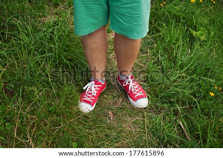 Legs men dressed in red sneakers on green grass