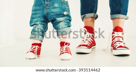 legs mother and child on a white background dressed in blue jeans and red sneakers legs mother and child on a white background dressed in blue jeans and red sneakers in a standing position - stock photo