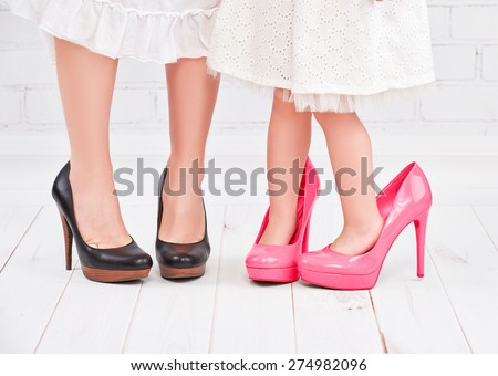 legs mother and daughter little girl fashionista in pink shoes on high heels - stock photo