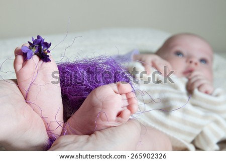 legs newborn baby in hands mother closeup with flowers