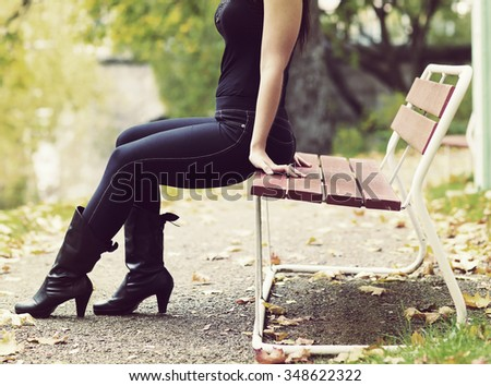 Legs of a beautiful woman while she is sitting in the park on a red bench. The woman is wearing high black shoes and jeans. Image taken during autumn time and image has a vintage effect applied. - stock photo