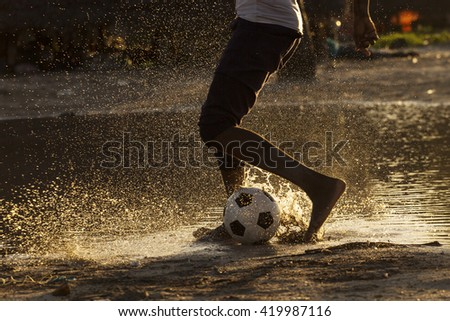 Legs of a black child playing footbal in water at sunset