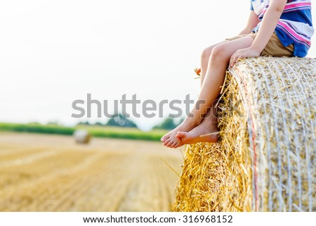 Legs of a kid traditional German bavarian clothes, leather shorts and check shirt. Child sitting on hay stack or bale and dreaming. Active outdoors leisure with children on warm summer day. - stock photo