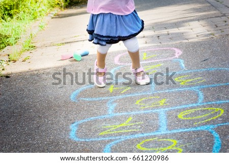 legs of a little girl playing hopscotch on the street