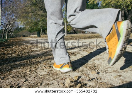 Legs of a man running on a dirt road in a park during an autumn