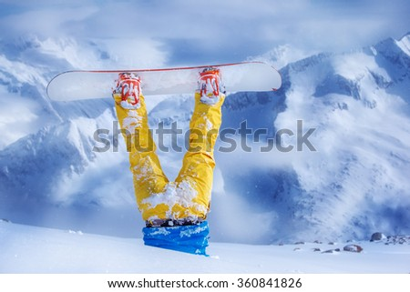 Legs of a snowboarder in yellow trousers stuck in deep snow upside down - stock photo