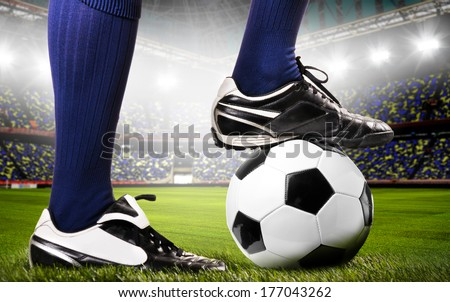legs of a soccer or football player on ball on stadium - stock photo