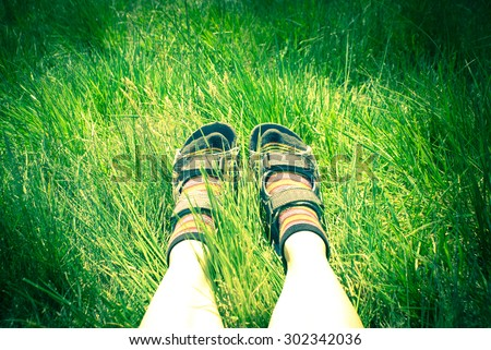Legs of a woman hiker in the trekking shoes in the grass. Image toned. - stock photo