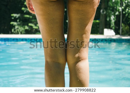 Legs of a woman standing in front of a swimming pool - stock photo