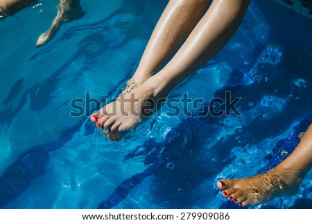Legs of a women in swimming pool water - stock photo