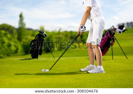 Legs of boy golfer with golf club at golf course at summer day - stock photo