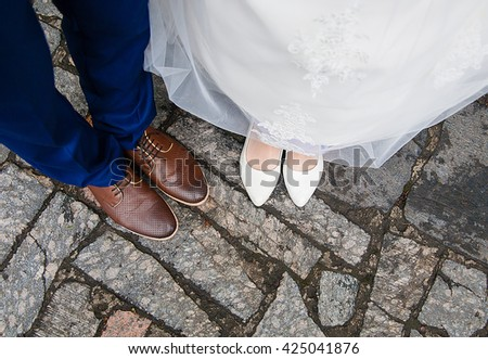 legs of bride and groom and their bridal shoes. - stock photo