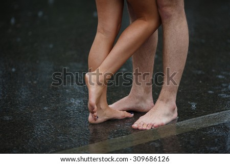Legs of couple standing on the asphalt road in the rain