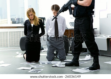 Legs of criminal with gun pointed at scared man and woman in office - stock photo