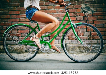 Legs of female bicyclist riding on background of brick wall