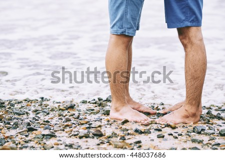 Legs of gay couple kissing on the beach