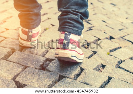 Legs of girl in gumshoes on pavement. Toned image - stock photo