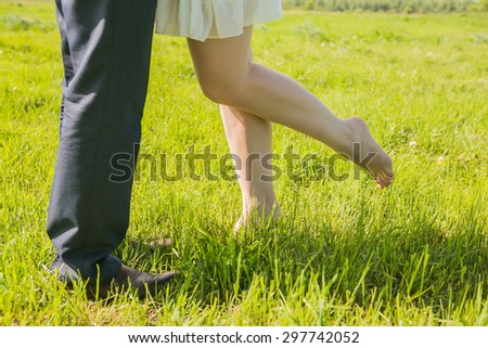 Legs of in loved couple kissing outdoors at the park - stock photo