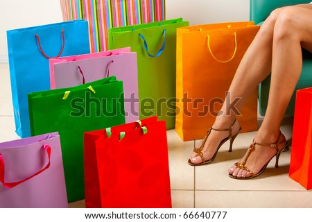 Legs of lady sitting surrounded by colorful paper bags - stock photo