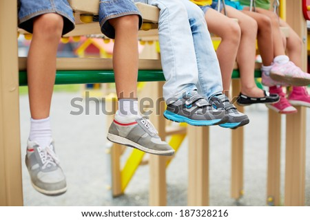 Legs of little friends sitting on swing or other recreational facility - stock photo