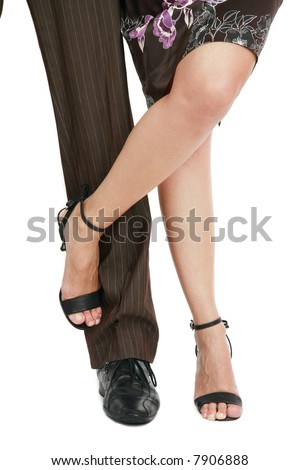 Legs of man in well-creased trousers and of beautiful woman in silk dress and stilettos - stock photo